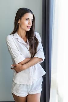 Jonge glimlachende vrouw die bij gezellig huis ontspannen, gelukkig voelen, rustend in de ochtend, kijkend door het venster
