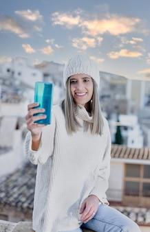 Jonge glimlachende vrouw die een foto met haar mobiele telefoon neemt tijdens de zonsondergang.