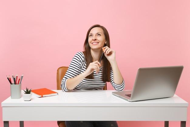 Jonge glimlachende vrouw die een potlood vasthoudt en opkijkt terwijl ze dromend zit te werken aan een wit bureau met een moderne pc-laptop