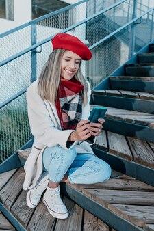 Jonge glimlachende vrouw die een sms-bericht schrijft met haar mobiele telefoon tijdens zonsondergang.