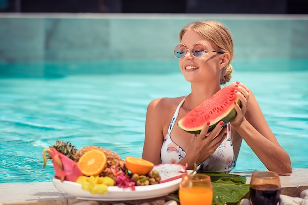 Jonge glimlachende vrouw die in de blauwe pool drijft en verse watermeloen in haar handen houdt