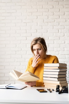Jonge glimlachende vrouw die in gele sweater een boek leest dat geschokt of verrast kijkt