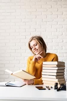Jonge glimlachende vrouw die in gele sweater een boek leest en lacht