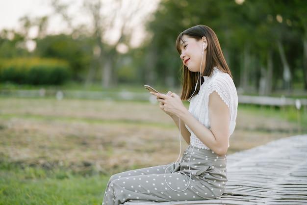 Jonge glimlachende vrouw die in witte kleren met oortelefoons op houten gang in het park zitten terwijl het gebruiken van mobiele telefoon die aan muziek luisteren met ogen kijkend vanaf camera in de stemming ontspannend en gelukkig