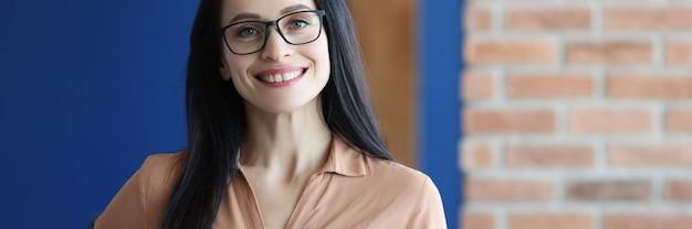 Jonge glimlachende vrouw die met glazen mok met koffie houdt