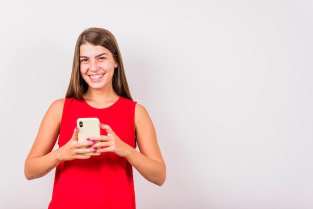 Jonge glimlachende vrouw die mobiele telefoon houdt