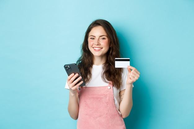 Jonge glimlachende vrouw die online betaalt, online winkelt met creditcard en smartphone in handen, tevreden naar de camera kijkt, staande over blauwe achtergrond