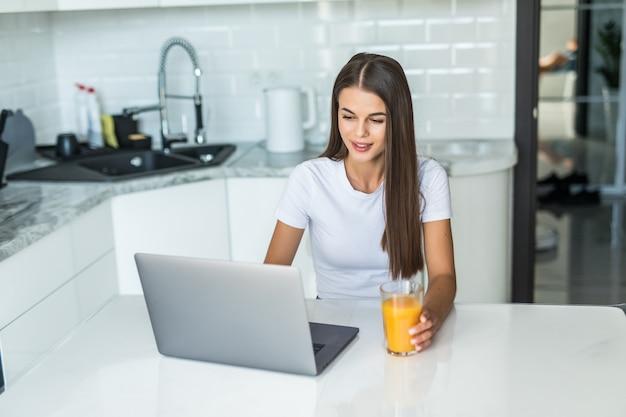 Jonge glimlachende vrouw die ontbijt in de keuken heeft die aan laptop verbindt en een gezond jus d'orange drinkt