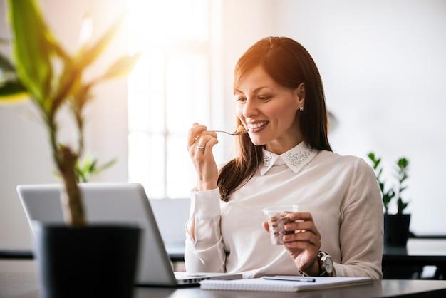 Jonge glimlachende vrouw die roomijs in bureau eet