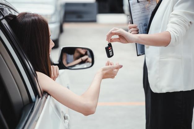 Jonge glimlachende vrouw die sleutel van een nieuwe auto krijgt.