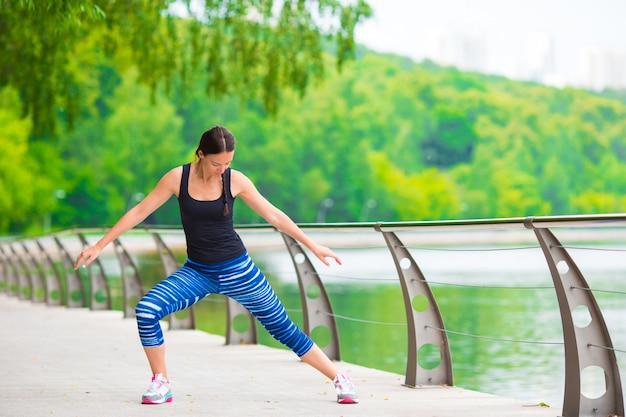 Jonge glimlachende vrouw die sportieve oefeningen in openlucht doet
