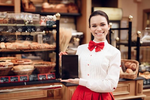 Jonge glimlachende vrouw die tablet in moderne bakkerij gebruiken.