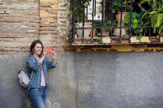 Jonge glimlachende vrouw die tegen een aardige muur leunen die haar mobiel houden. aantrekkelijk meisje fotograferen met haar smartphone op straat