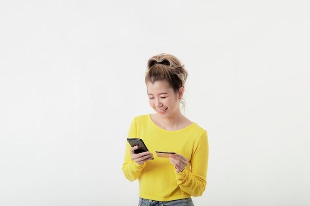Jonge glimlachende vrouw die telefoon en het aantal creditcard gebruikt om online te winkelen