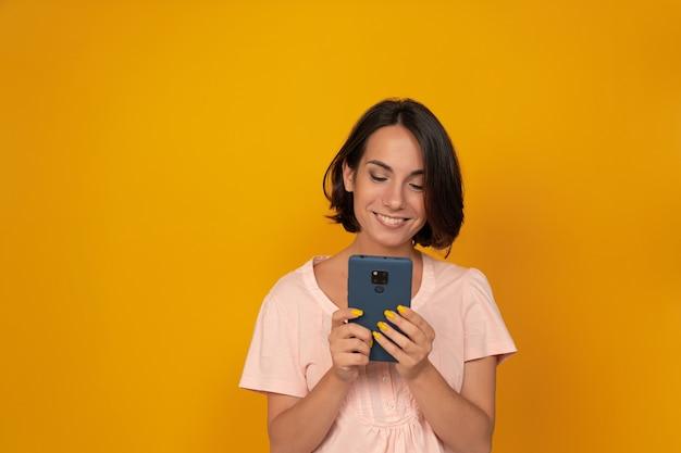 Jonge glimlachende vrouw die telefoon met behulp van