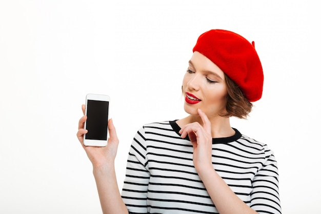 Jonge glimlachende vrouw die vertoning van mobiele telefoon toont.