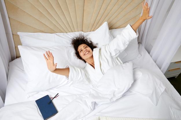 Jonge glimlachende vrouw die wakker wordt in bed en haar armen uitrekt concept van gelukkig begin van de?