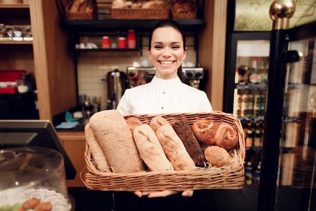 Jonge glimlachende vrouw die zich met brood in bakkerij bevindt.