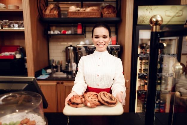 Jonge glimlachende vrouw die zich met broodjes in bakkerij bevindt