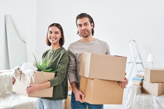 Jonge glimlachende vrouw en haar echtgenoot met ingepakte dozen die zich in huismilieu bevinden