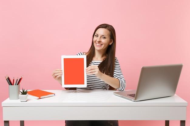 Jonge glimlachende vrouw houdt tabletcomputer vast met een leeg leeg scherm en zit aan een wit bureau met een moderne pc-laptop