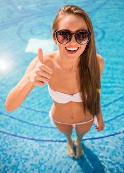 Jonge glimlachende vrouw in bikini in zwembad.