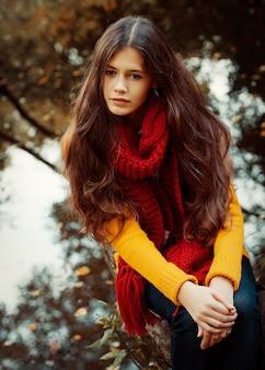 Jonge glimlachende vrouw in de herfstpark