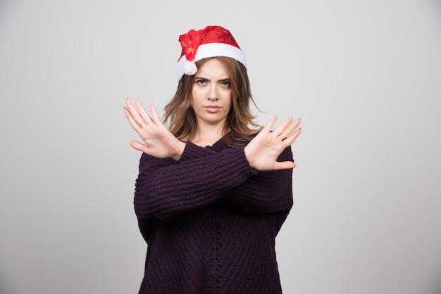 Jonge glimlachende vrouw in de hoed van de kerstman die stopbord met handen toont.