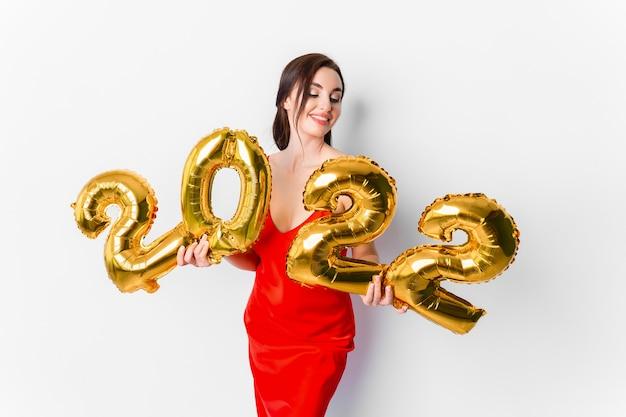 Jonge glimlachende vrouw in rode cocktailjurk met lichte make-up die nieuwjaar viert en gouden...