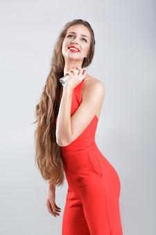 Jonge glimlachende vrouw in rode jurk die parfum op haar nek toepast
