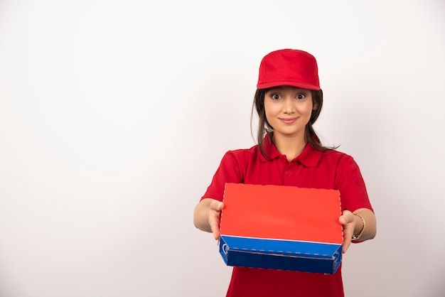 Jonge glimlachende vrouw in rood uniform die pizza in doos levert.