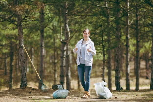 Jonge glimlachende vrouw in vrijetijdskleding die afval schoonmaakt en duimen opsteekt in park of bos
