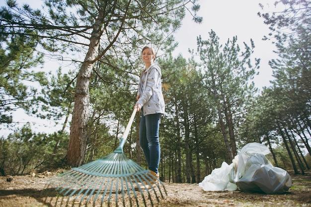 Jonge glimlachende vrouw in vrijetijdskleding die afval schoonmaakt met een hark voor het ophalen van afval in een bezaaid park. probleem van milieuvervuiling