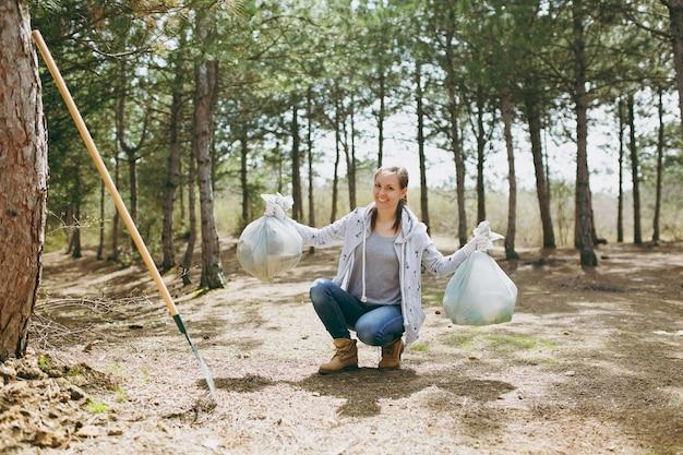 Jonge glimlachende vrouw in vrijetijdskleding die afval schoonmaakt met vuilniszak in park of bos