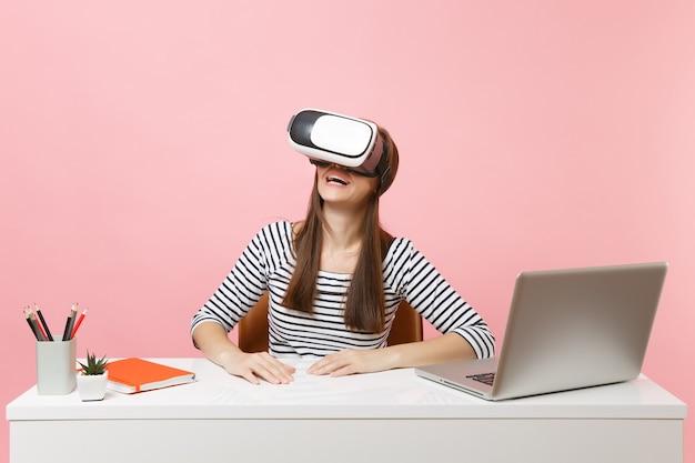 Jonge glimlachende vrouw in vrijetijdskleding, headset van virtual reality op hoofd zit en werkt aan een wit bureau met pc-laptop