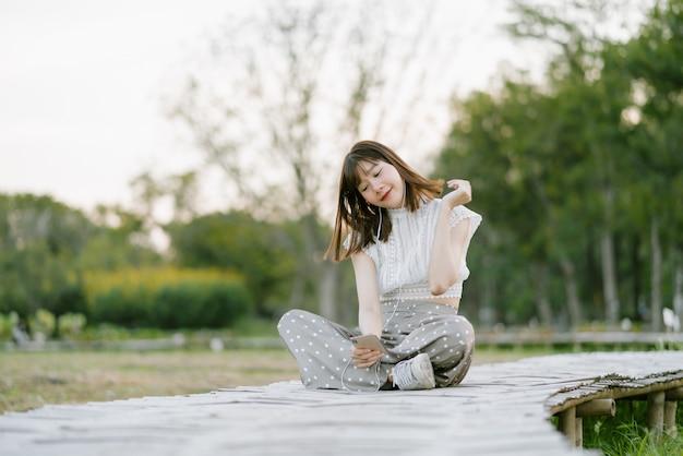 Jonge glimlachende vrouw in witte kleren met oortelefoons die op houten gang in het park zitten en van haar ogenblik genieten terwijl het gebruiken van mobiele telefoon luisterend naar muziek met haar ogen bekijkend het scherm