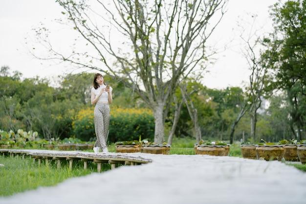 Jonge glimlachende vrouw in witte kleren met oortelefoons gebruikend mobiele telefoon luisterend aan muziek met haar ogen bekijkend het scherm genietend van haar ogenblik terwijl het wandelen op houten gang in het park