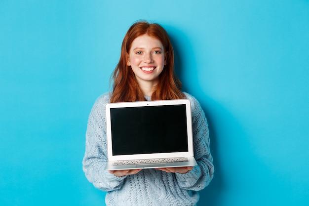Jonge glimlachende vrouw met rood haar en sproeten die computerscherm tonen, laptop houden en online promo demonstreren, die zich over blauwe achtergrond bevinden.