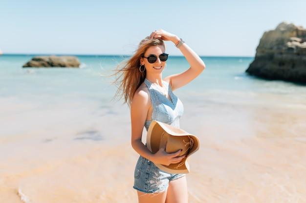 Jonge glimlachende vrouw op vakantie met zonnehoed en glazen.