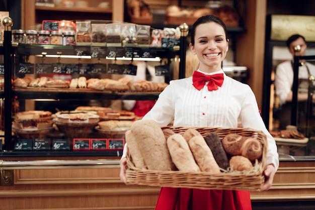 Jonge glimlachende vrouw permanent met brood in bakkerij.