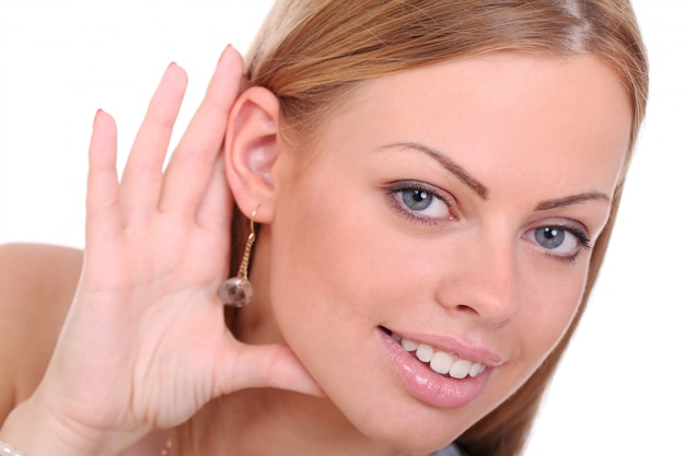 Jonge glimlachende vrouw probeert te luisteren