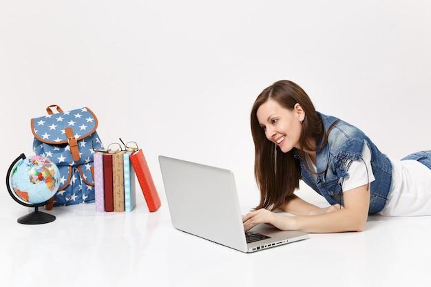 Jonge glimlachende vrouw student in denim kleding bezig met laptop pc computer liggend in de buurt van globe rugzak en schoolboeken geïsoleerd
