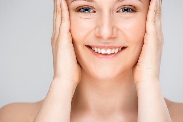 Jonge glimlachende vrouw zonder vlekken