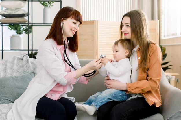 Jonge glimlachende vrouwelijke arts die weinig babymeisje op de wapens van de moeder thuis onderzoekt