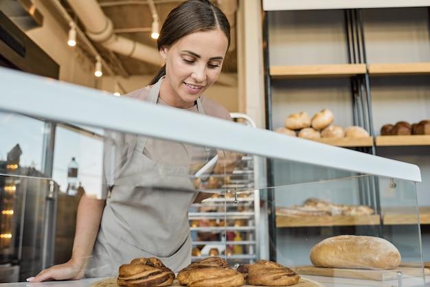 Jonge glimlachende vrouwelijke klerk die bij het display staat met het bakkerijassortiment en de broodjes controleert