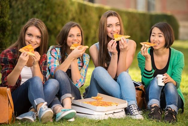 Jonge glimlachende vrouwelijke studenten zitten op de grond.