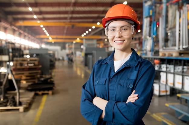 Jonge glimlachende vrouwelijke technicus in blauwe uniforme, beschermende brillen en helm die in moderne fabriek werken