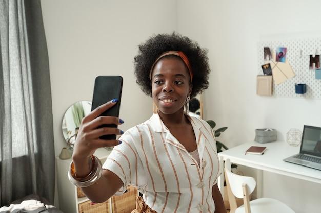 Jonge glimlachende vrouwelijke thuiskantoormedewerker die selfie maakt