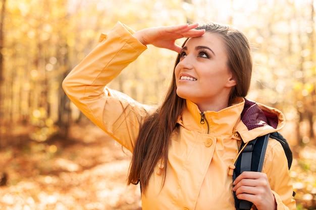 Jonge glimlachende vrouwelijke wandelaar die ver weg kijkt