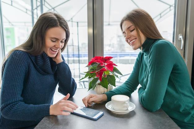 Jonge glimlachende vrouwen die in koffie spreken
